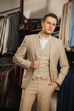 Elegant young handsome man. A young stylish man in a blue cloth jacket. It is in the showroom, trying on clothes, posing. Advertis Royalty Free Stock Images