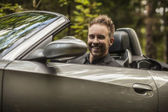 Elegant young happy man in convertible car outdoor. Stock Photos