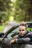 Elegant young happy man in convertible car outdoor. Stock Image