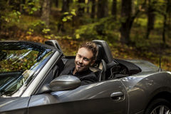 Elegant young happy man in convertible car outdoor. Royalty Free Stock Image