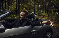 Elegant young happy man in convertible car outdoor. Stock Images