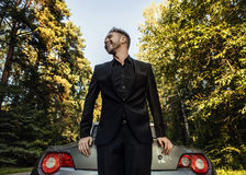 Elegant young happy man in convertible car outdoor. Stock Photos