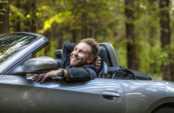 Elegant young happy man in convertible car outdoor. Royalty Free Stock Photo