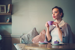Elegant young lady alone in a cafe.  Royalty Free Stock Image