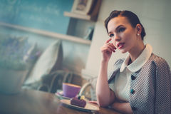 Elegant young lady alone in a cafe.  Royalty Free Stock Photography