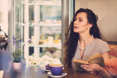 Elegant young lady alone in a cafe Stock Image
