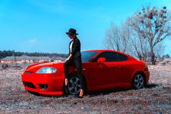 Elegant young lady in hat with wide brim sits on a red sport car. In the field royalty free stock photography