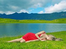Elegant young lady in the mountains. Elegant young lady in a red dress in a mountain lake Stock Images