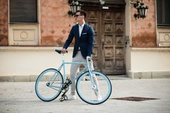 Elegant young man with bicycle. Portrait of an elegant young man with blue bicycle outdoors on the street Stock Photos