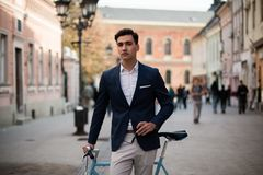 Elegant young man with bicycle. Portrait of a young handsome and elegant man in blue suit with bicycle outdoors, on the street Stock Images