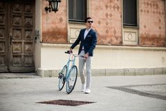 Elegant young man with bicycle. Portrait of a young handsome and elegant man in blue suit with bicycle outdoors, on the street Stock Photography