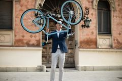 Elegant young man with bicycle. Portrait of an elegant young man holding his blue bicycle outdoors on the street Stock Photography