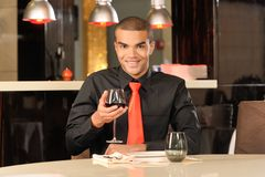 Elegant young man holding glass of red wine. Royalty Free Stock Photos
