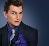Elegant young man in jacket. Fashion model. Portrait of a young man in a jacket and a flower Stock Photos