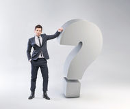 Elegant young man leaning against the question mark Stock Images