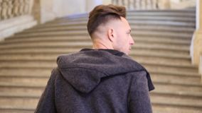 Elegant young man on old marble stairs. Elegant attractive young man outdoor wearing coat, walking up old marble stairs in European city stock video