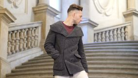 Elegant young man on old stone stairs. Elegant attractive young man outdoor wearing coat, walking down on old stairs in European city stock video footage