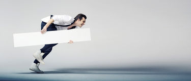 Elegant man running with a white board. Elegant young man running with a white board Royalty Free Stock Image