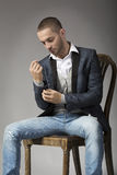 Elegant young man in  sitting on a stool while buttoning his sle. Eve, warm colours Royalty Free Stock Photography
