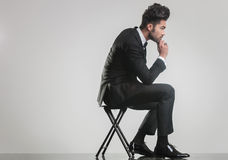 Elegant young man sitting on a stool and thinking Royalty Free Stock Images