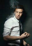 Elegant young man smoking Royalty Free Stock Photography