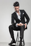 Elegant young man stitting on a stool while looking down Stock Image