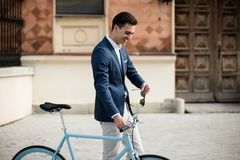 Elegant young man in suit with bicycle. Portrait of a young handsome and elegant man in blue suit with bicycle outdoors, on the street Stock Photos