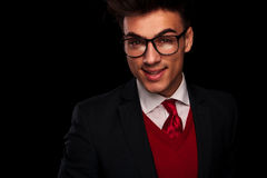 Elegant young man in suit wearing glasses. Close portrait of elegant young man in suit wearing glasses, posing smiling at the camera in dark studio background Royalty Free Stock Images