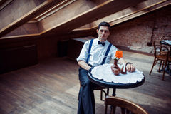 Elegant young man in suspenders and glasses in cafe.  Royalty Free Stock Images