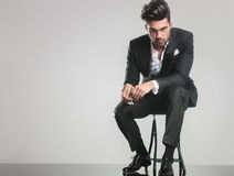 Elegant young man in tuxedo sitting on a stool Royalty Free Stock Images