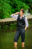 Elegant young man using cell phone in a lake Royalty Free Stock Image