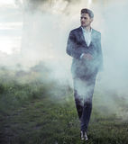 Elegant young man walking in the morning haze Stock Image