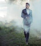 Elegant young man walking in the morning haze. Elegant young guy walking in the morning haze stock image