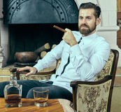 Elegant young man with whiskey and cigar. Young man with beard having a glass of scotch and a cigar Stock Photo