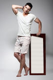Elegant Young Man in White Cotton Clothes with Board Standing Stock Photography
