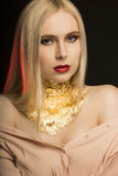 Elegant young model with long blonde hair and golden foil on her stock photos