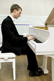 Elegant young pianist playing piano Royalty Free Stock Photos