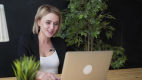 Elegant young positive beautiful girl sitting using laptop computer in a cafe.  stock footage