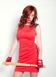 Elegant young redhead woman in little red dress and red leather gloves, brandishing a baseball bat Stock Image