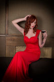 Elegant young redhead woman in a red dress, having a glass of red wine Stock Image