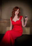 Elegant young redhead woman in a red dress, having a glass of red wine Royalty Free Stock Photo