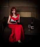 Elegant young redhead woman in a red dress, reads glamor magazine, having a glass of red wine.  Stock Image