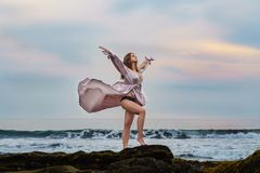 Elegant young woman in beautiful long dress waving in the wind with a deep neckline stay on ocean beach on the rock on sunset. In Bali Indonesia. Slim fabulous royalty free stock photography