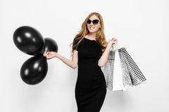 Elegant young woman in black dress with bags and black balloons, fun shopping, on white background. Shopping, Discounts, Black