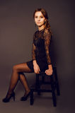 Elegant young woman in black lace dress with long curly hair Stock Image