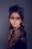Elegant young woman in black lace dress and veil hat with long c Royalty Free Stock Photo