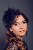 Elegant young woman in black lace dress and veil hat with long c Royalty Free Stock Images