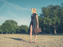 Elegant young woman with briefcase standing in park Stock Photography
