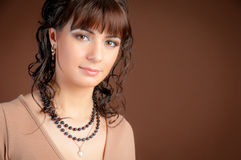 Elegant young woman on a brown background. Royalty Free Stock Image