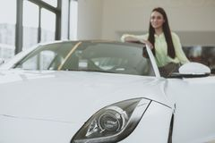 Elegant young woman buying new car at dealership royalty free stock photo